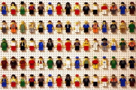 White wall with various Lego minifigs stuck to it in rows.