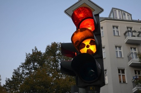 Traffic lights with red and amber lit up and a radioactivity sign on the amber.