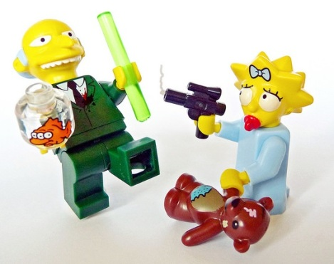 Lego Maggie Simpson holding a teddy bear and pointing a gun at Lego Mr. Burns, who is holding Blinky the fish and a carbon rod